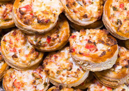 Delicious portioned round mini pies made of crispy puff pastry stuffed with green onion eggs and crab meat and melt cheese baked in the oven and stacked on a platter and ready for eating