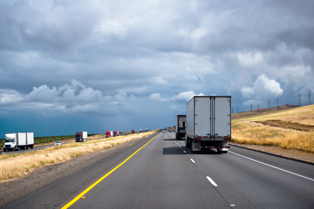 Convoy of different makes and models big rigs semi trucks with semi trailers driving in both directions by divided interstate highway in California with stormy gray cloud sky and sunny yellow hills Stock Photo