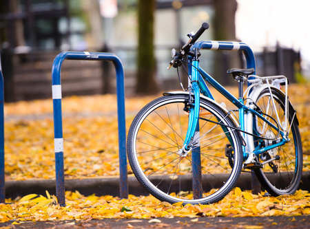Amateur blue bicycle whose owner prefer an active healthy lifestyle is parked on the city street with autumn fallen yellow leaves  in the down town of the modern bicycle city of Portland