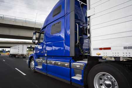 Big rig modern bright blue long haul semi truck with refrigerator semi trailer transporting perishable and frozen foods on the wide highway road with crossing bridge and another semi truck