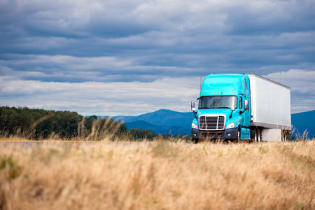 Blue modern bonnet powerful long haul big rig semi truck with dry van semi trailer transport commercial cargo for timely delivery on scenic road with grass forest mountain and cloudy sky