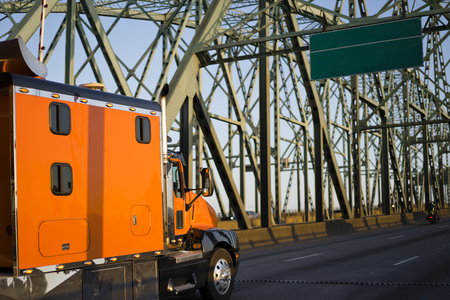 Orange big rig long haul semi truck with extra long cabin for truck driver rest driving alone interstate highway transporting commercial cargo moving on arched metal truss Columbia Interstate Bridge