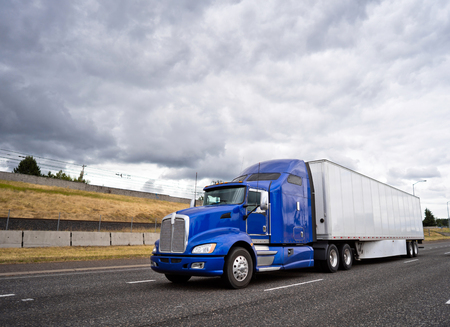 Classic dark blue big rig American popular bonnet semi truck with dry van semi trailer going on wide highway with stormy sky caring commercial cargo for delivery to business warehouse Stock Photo