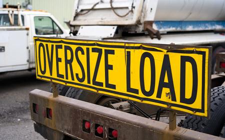 Letrero de carga de gran tamaño negro sobre amarillo Instalado en la parte trasera del tractor de camión de plataforma grande con parachoques de metal pesado para un soporte móvil de seguridad en el estacionamiento esperando la próxima carga de gran tamaño