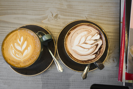 Two cups on the table. One cup of coffee, another cup with hot chocolate. Each drink is decorated with a milk pattern. A great opportunity to enjoy drinks and socializing