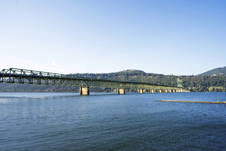 Long straight metal trusses Hood River Lifting White Salmon transportation Bridge with two towers for lifting arched section across Columbia River in sun shine and green hill with trees and houses Archivio Fotografico