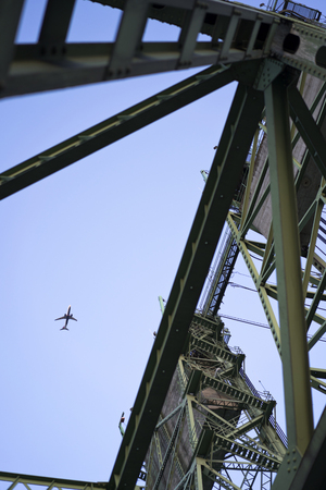 An airplane in the sky flies over Columbia Interstate lifting bridge with towers with concrete counterweights to raise the lifting part of the bridge and triangle trusses of this arched construction
