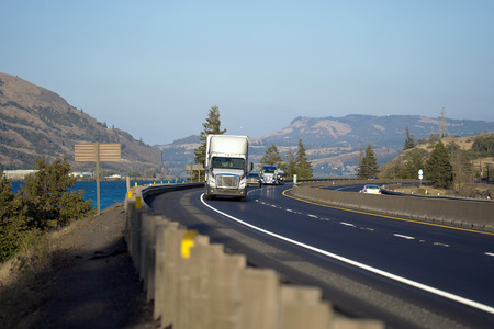 Trattore per semirimorchio bianco potente e potente che trasporta merci in un semirimorchio a secco che va in salita su una spettacolare strada tortuosa tra il fiume e le colline di fronte al traffico stradale