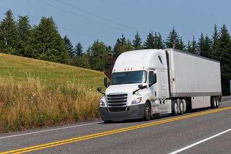 Camión blanco clásico Big Rig con furgoneta seca semirremolque duro de tamaño completo que conduce cuesta abajo en la sinuosa carretera con bosque y pradera a los lados en la niebla del aire caliente del verano
