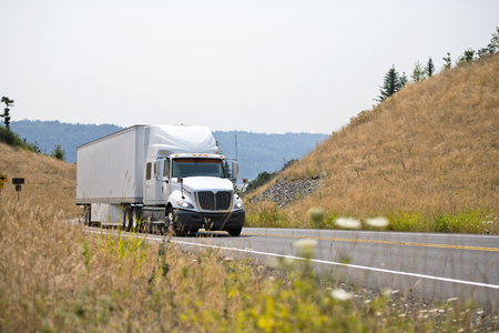 White powerful big rig semi truck tractor transporting goods in dry van semi trailer going uphill on spectacular winding road between the hills with dried grass and mist of hot summer air