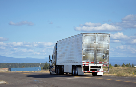 Dark big rig modern professional popular semi truck transporting perishable food in chilled refrigerated semi trailer running on divided local road with river view and clouds for delivery goods