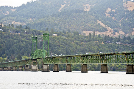 Landscaping panorama of Long truss drawbridge with an elevating arched section across the Columbia River in the Hood River Columbia Gorge area with road traffic and green hills hidden in the haze