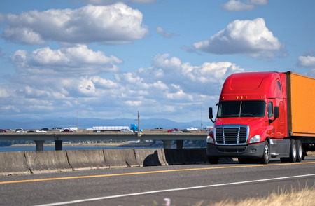 Powerful red big rig semi truck with container on flat bed semi trailer transporting commercial cargo and moving on the road along the river with bridge at stunning natural Columbia Gorge aria Stock Photo