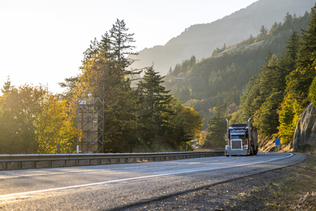 Big rig classic American idol bonnet dark semi truck with tall exhaust pipes transporting cargo on the amazingly picturesque winding autumn road in Columbia River Gorge¬ in sunlit