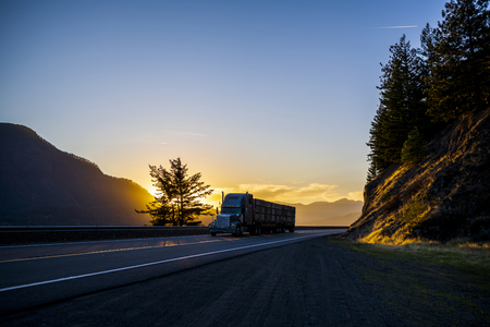 Silhouette of big rig American bonnet powerful classic semi truck transporting stocked fruit boxes on flat bed semi trailer running on highway with mountain in sunset Stockfoto
