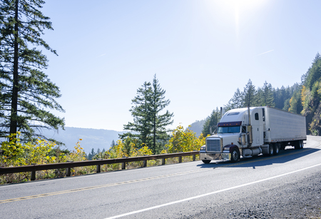 Big rig American powerful white classic semi truck transporting cargo in refrigerated semi trailer on winding autumn road in Columbia River Gorge in Washington Stock Photo