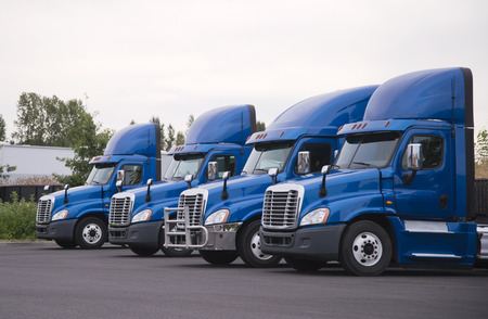 Side view of the blue big rigs semi trucks tractors with high roof spoiler for better aerodynamic flow stand in row without semi trailers on the parking lot and waiting for loading cargo for delivery