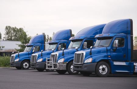 Widok z boku na niebieskie ciągniki siodłowe z dużymi platformami z wysokim spojlerem dachowym dla lepszego przepływu aerodynamicznego, stoją w rzędzie bez naczep na parkingu i czekają na załadunek ładunku do dostawy