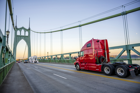 Bright red bonnet big rig semi truck tractor with high cab running on the St Johns Bridge with another traffic across Willamette river in industrial area of Portland to warehouse for pick up trailer Banco de Imagens