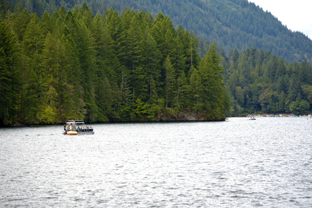 Picturesque mountain clear water deep Merwin Lake with evergreen coniferous forests on the mountains and the curvy shore and a floating boat with tourists – best place to healthy rest