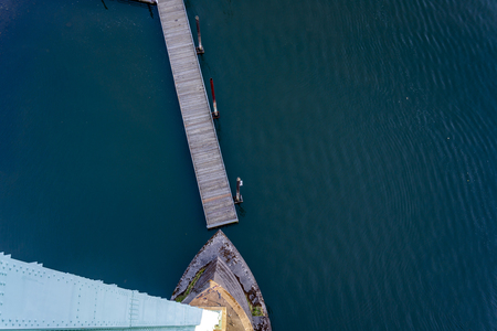 Top view of the support of the gothic St Johns bridge over the Willamette River in Portland with a small floating pier with pillars for mooring boats and yachts and dark water surface