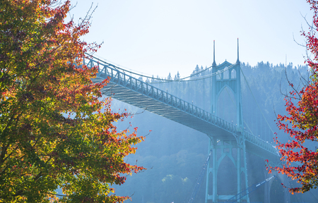 Famous gothic St Johns bridge across the Willamette River in Portland industrial area with arched support pillars surrounded by autumn colorful trees is a real pride of the Portland people Stock Photo