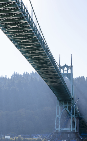 High powerful arch support of a gothic style transport St Johns Bridge with windows at the top and stretch marks that support the bridge across Willamette River in Portland industrial area Banco de Imagens