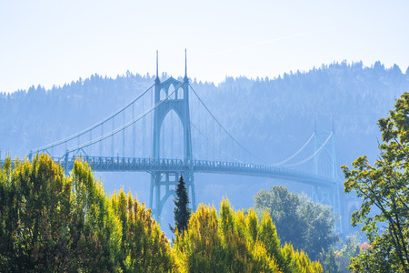 Popular gothic St Johns bridge with haze across the Willamette River in Portland industrial area with arched support pillars surrounded by autumn colorful trees is a real pride of the Portland people Stock Photo