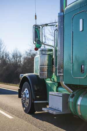Part of big rig bright green classic American semi truck with extended cab for long haul routs transporting semi trailer driving on the straight highway in sunny day