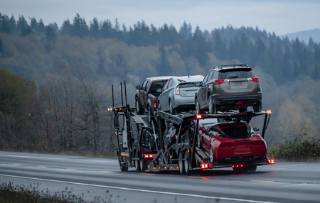 Car transportation by big rig semi truck allows all dealerships to ensure uninterrupted sale of new and used cars ensuring consumer demand in any state of America. Trucks carry out the main freight Stock Photo - 113942075