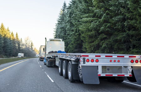 Big rig long haul powerful semi truck with empty light weight aluminum flat bed semi trailer running on the winter road in convoy with another semi trucks and evergreen trees Reklamní fotografie