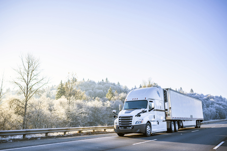 Big rig white technological improved long haul semi truck with refrigerated semi trailer for transportation of perishable and frozen food going on the winter road with snowy frost trees on the hill Stock fotó