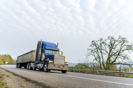 Classic blue big rig American bonnet powerful semi truck driving with covered bulk ribbed semi trailer transporting commercial cargo on the winding autumn road