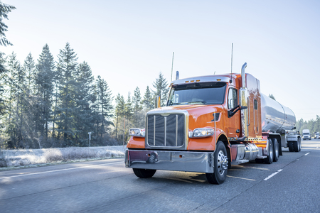 Orange big rig American bonnet long haul semi truck with long cylindrical tank semi trailer transporting liquid and liquefied chemical cargo on the winter frosty road 免版税图像 - 113941350