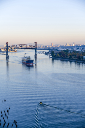 Large Sea transportation multi-ton dry cargo ship loaded with commercial cargo moves under raised drawbridge along the Willamette River in the background of evening Portland down town view Stock Photo