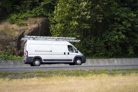 White popular compact cargo transportation mini van comfortable for commercial use for small business or local delivery driving with ladders on the roof on the road with trees and nature rock wall 写真素材
