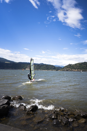 The surfer enjoying a walk with sail under the fresh wind along the Columbia River in the Hood River - the center of windsurfing as a professional sport, and the resting place for windsurfing lovers Banco de Imagens