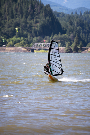 The surfer enjoying a walk with sail under the fresh wind along the Columbia River in the Hood River - the center of windsurfing as a professional sport, and the resting place for windsurfing lovers 免版税图像