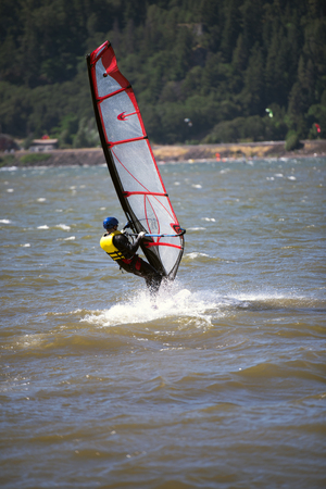 The surfer enjoying a walk with sail under the fresh wind along the Columbia River in the Hood River - the center of windsurfing as a professional sport, and the resting place for windsurfing lovers