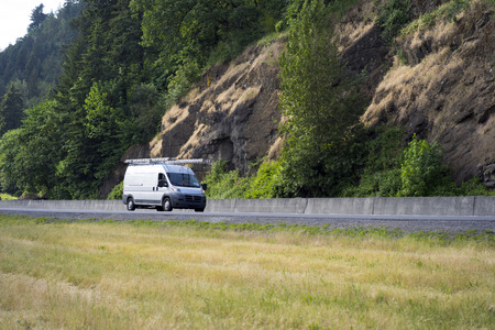 White popular compact cargo transportation mini van comfortable for commercial use for small business or local delivery driving with ladders on the roof on the road with trees and nature rock wall Stock Photo