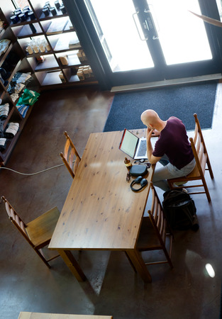 A man in t-shirt working on a laptop is closely watching changes on the