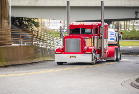 Big rig bright red classic American idol semi truck for long haul routs with high chrome exhaust pipes transporting semi trailer driving on the city street intersection turning under railroad bridge