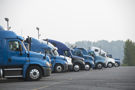 Profiles of different big rig long haul semi trucks with high cab standing on parking lot waiting for loading and possibility of continuing to the destination according to approved schedule Stok Fotoğraf