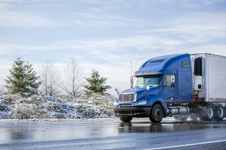 Big rig pro long haul blue semi truck tractor transporting commercial cargo in refrigerator semi trailer going on the wet glossy road with water from melting snow and winter snowy trees on the side