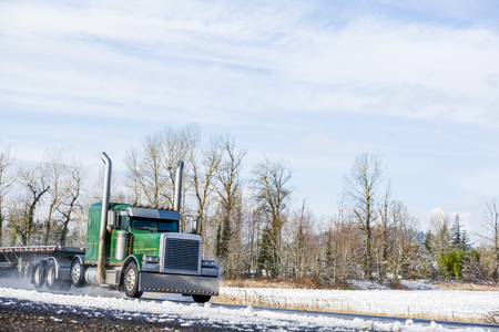 Big rig long haul semi truck tractor transporting empty semi trailer going to warehouse for loading cargo running on wet glossy road with water from melting snow and winter snowy trees on the hill