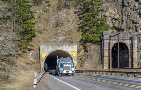 Big rig long haul blue American semi truck transporting commercial cargo on step down semi trailer running through the tunnel on the narrow road along the Columbia River in Columbia River Gorge