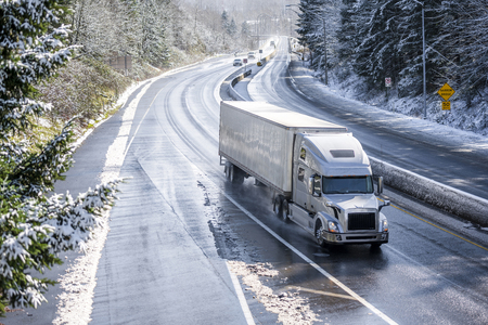 Big rig long haul gray semi truck tractor transporting commercial cargo in dry van semi trailer going on the wet slippery road with water from melting snow and winter snowy trees on the hills Фото со стока