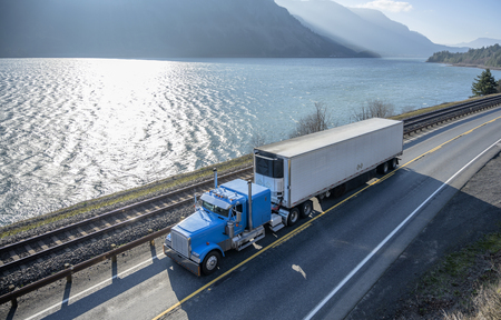 Big rig long haul bonnet American semi truck transporting commercial cargo in refrigerated semi trailer running on the narrow road along the Columbia River and mountain in Columbia River Gorge