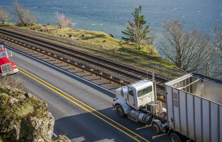 Big rig low cab economical long haul bonnet semi truck transporting commercial cargo in bulk semi trailer running on the narrow road along the Columbia River in Columbia River Gorge
