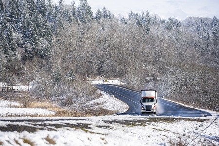 Big rig day cab semi truck tractor transporting commercial cargo in covered bulk semi trailer going on the wet slippery road with water from melting snow and winter snowy trees on the hills Stock Photo - 116955575